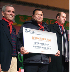 School principal holding wall plaque in recognition of Italcementi's contribution. He is flanked by CSF Executive Director Ben Frankel (on left) and Pierre Eloy