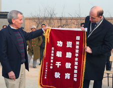 Ben Frankel and Pierre Eloy with banner in recognition of the occasion, reading: Support for education is a contribution that lasts for a thousand years.