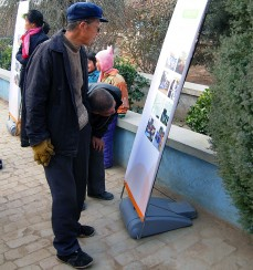 Villagers examining display board documenting the transformation of schools and volunteer activities at the schools.